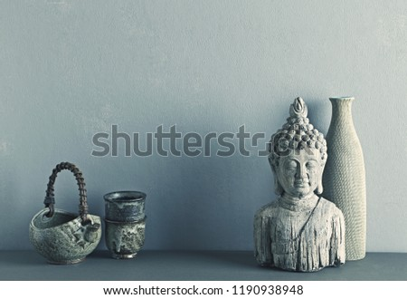 An arrangement of hand crafted Asian ceramics and a stone Buddha statue. Copy space. Gray background