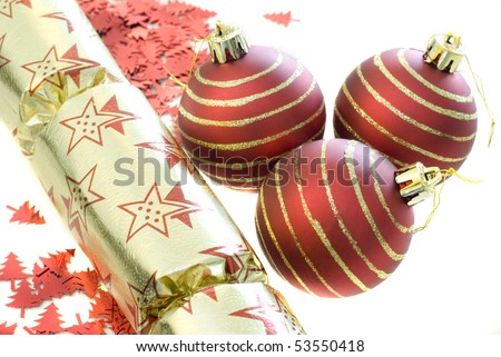 an arrangement of seasonal decorations, baubles, confetti shapes and a christmas cracker