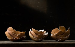 An arrangement of 3 stacks of broken brown eggshells with a black background.