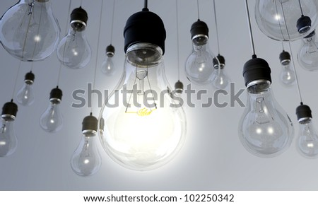 An array of hanging light bulbs with the main one turned on