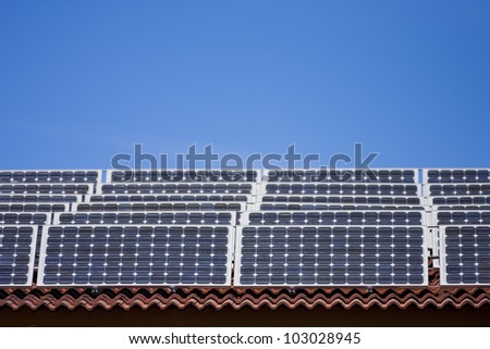 An array of solar panels on a roof, with blue sky