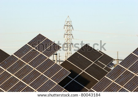An array of solar panels with an electric tower in the background