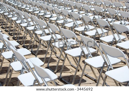 An array of white chairs waiting for the audience of an open-air event