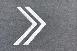 An arrow pointer is drawn with white paint on the road. Sign of turning to the right on the asphalt, direction of movement, path to follow. Background with copy space.