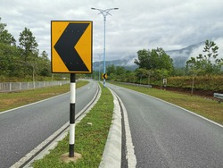 An arrow signage board on the small road.