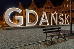 An art work with the name of the city of Gdansk, Poland eluminated in the night.