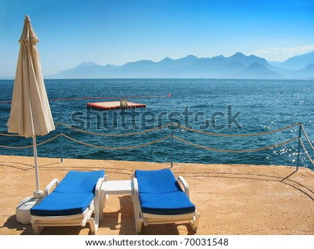 An artificial beach territory with two beach chairs and floating platform in the sea