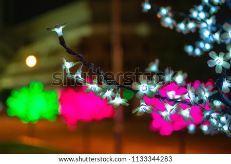 An artificial tree glows at night, a soft glowing decorative light. Against the backdrop of a dark street. Night, Penang, Malaysia #1133344283