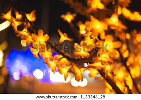 An artificial tree glows at night, a soft glowing decorative yellow ornament. Against the backdrop of a dark street. Night, Penang, Malaysia #1133346128