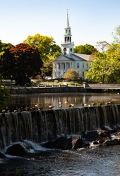 An artificial waterfall with ducks are sitting on the edge, and the white building of the church has a roof with a steeple - tower, belfry, lantern, spire among green trees on a sunny day.