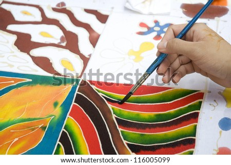 An artist carefully paint the pattern on a white traditional batik fabric