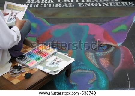 An artist creates artwork of a dog with chalk at the I Madonnari Italian Street Painting Festival at Santa Barbara Mission in Santa Barbara, California, in May 2005.