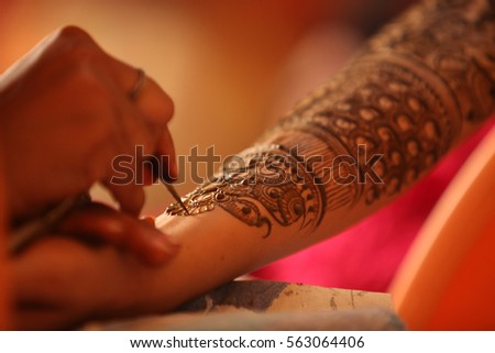 An artist making a beautiful henna or mehendi design on the hand of an Indian wife. Stock photo ©
