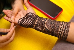 An Artist performing mehandi design on female hand close up image