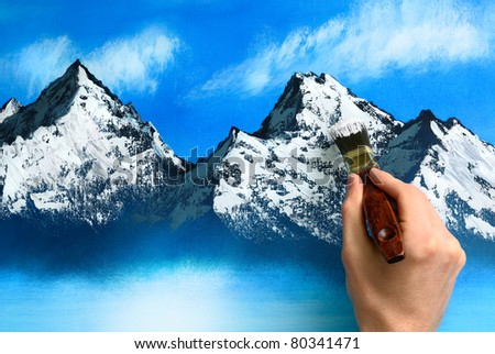 An artist's hand holding a brush and painting a mountain scenery on a canvas