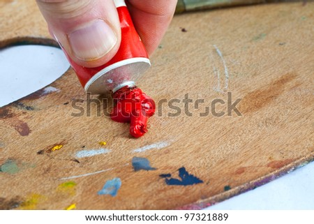 An artist squeezes out some red paint from a tube of oil paint.