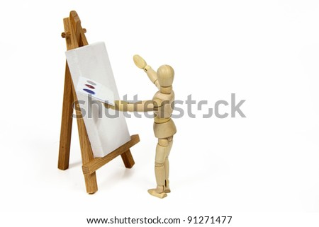 An artist (wooden doll) painting on canvas