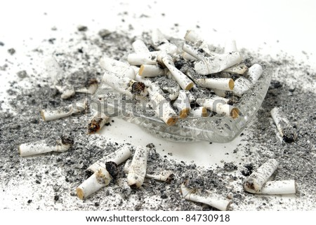 An ashtray is overflowing with burnt cigarette butts.
