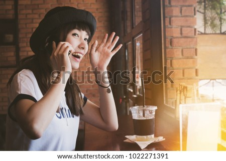 an Asia beautiful woman using mobile phone and  wave hand  smiling  looking outside the window  of  cafe,coffee shop with fun and happy. #1022271391