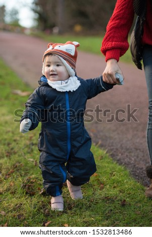 An Asian baby wearing winter clothes, a fox hat and mittens holds her mom's hand while smiling and walking on grass in Princes Street Gardens, Edinburgh, Scotland, UK