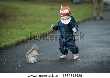 An Asian baby wearing winter clothes, mittens and a fox hat walks slowly towards a brown squirrel eating In Princes Street Gardens, Edinburgh, Scotland, UK
