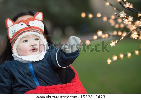 An Asian baby with teary eyes wearing winter clothes, mittens and a fox hat reaches out to Christmas light decorations on a tree In Princes Street Gardens, Edinburgh, Scotland, UK