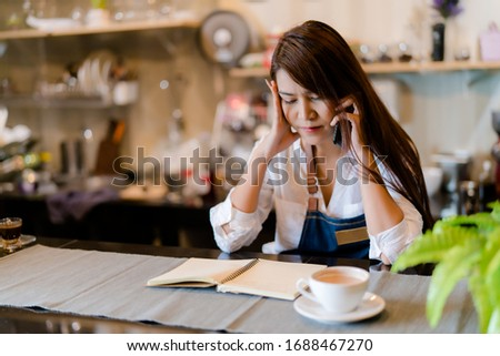 An Asian barista woman is stressed because of economic conditions and COVID-19 or Coronavirus has caused her sales in the coffee shop to drop dramatically, the impact of a small self-employed business