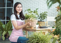An asian beautiful woman smiling with happiness while gardening and holding plants as her hobby at home
