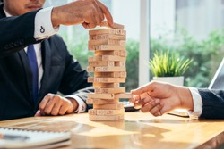 An asian businessman arraging the small wooden blocks on his working desk by close-up, Business construction and fail concept.