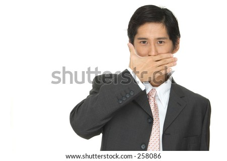 An asian businessman in a grey suit with his hand across his mouth