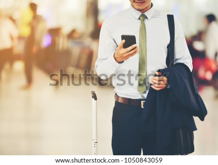 An Asian businessman is using a smartphone to get in business while waiting for a trip in the airport.This image is Soft focus. #1050843059