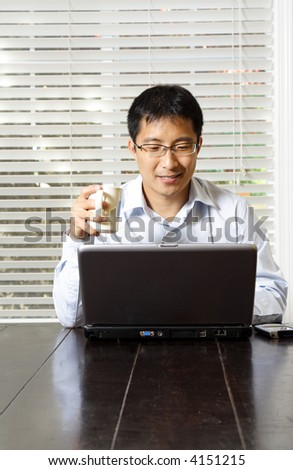An asian businessman working on his laptop - stock photo
