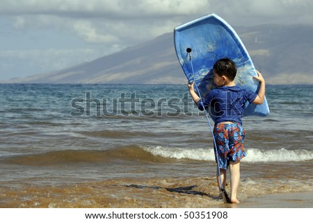 An Asian Child carrying a boogie board