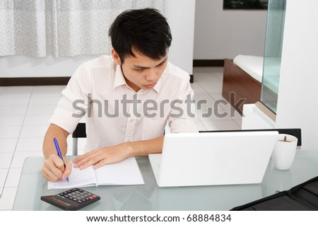 An Asian college student doing homework at home