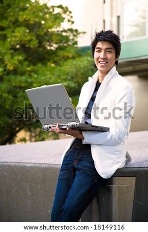 An asian college student holding a laptop at the campus