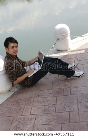 An Asian college student working with his laptop beside a lake