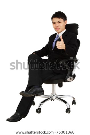 An Asian executive showing thumbs up while sitting on a chair and isolated in white background