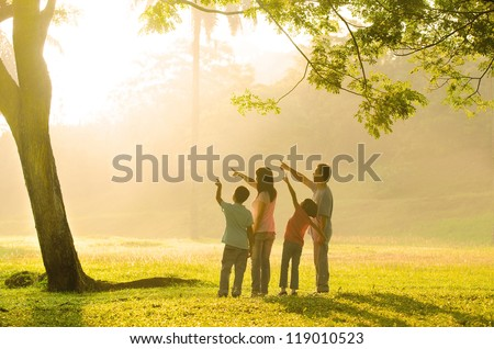 an asian family pointing to somewhere during a beautiful sunrise, backlight