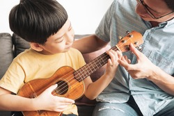An asian father joyful teaching his little boy to play ukulele a small, guitar-like instrument in the living room. Family bonding, Child brain development, neuroscience, Activities, Father's day.