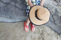 An Asian girl in dark blue and yellow floral pattern holds a big straw hat and bright red shoes. The child sits on a rock with his feet on the wet sand.