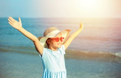 An Asian girl opens her arms and stands happily on the summer beach.