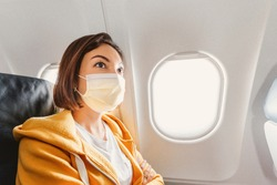 An Asian girl wears a medical face mask during an airplane flight. Concept of safety and new rules of conduct for air transport passengers