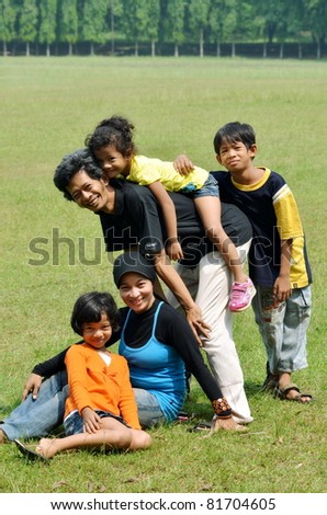 An asian happy family posing together in outdoor scene - stock photo