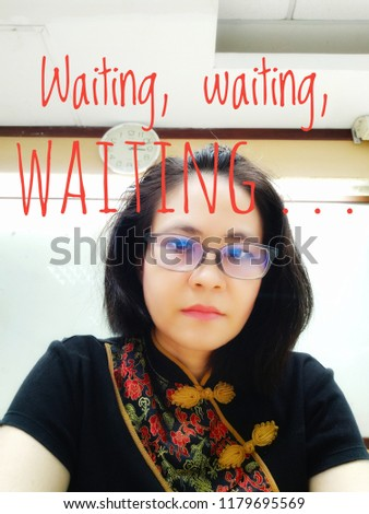 An Asian lady in Chinese neck dress and a clock in the back with description, waiting, waiting waiting . . .   #1179695569
