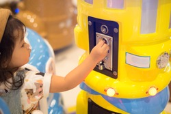 An Asian little girl use her hand  to insert a token or coin into the slot to play an electronic toy and game in the Kid gaming zone. (Focus on insert slot)