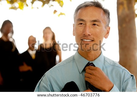 An asian looking business man with colleagues in the background