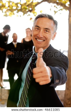 An asian looking business man with thumbs up - critical focus on eyes