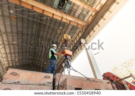 An Asian male engineer wearing protective equipment controlling electric cable hoist, heavy hoist iron hook lifting of structure platform and large steel box in a factory. Low angle view.