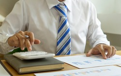 An Asian male finance worker uses a calculator to calculate corporate tax expenses after deducting profits. On the table in the office, budget finance and tax ideas.