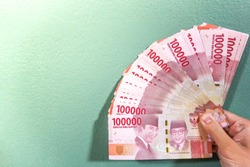 An Asian male hand is holding bunches of Indonesian Rupiah (IDR) Red 100,000 bank notes currency with light green and bright sunlight background